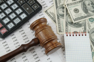 money, calculator, gavel and spreadsheet representing hoa dues post bankruptcy